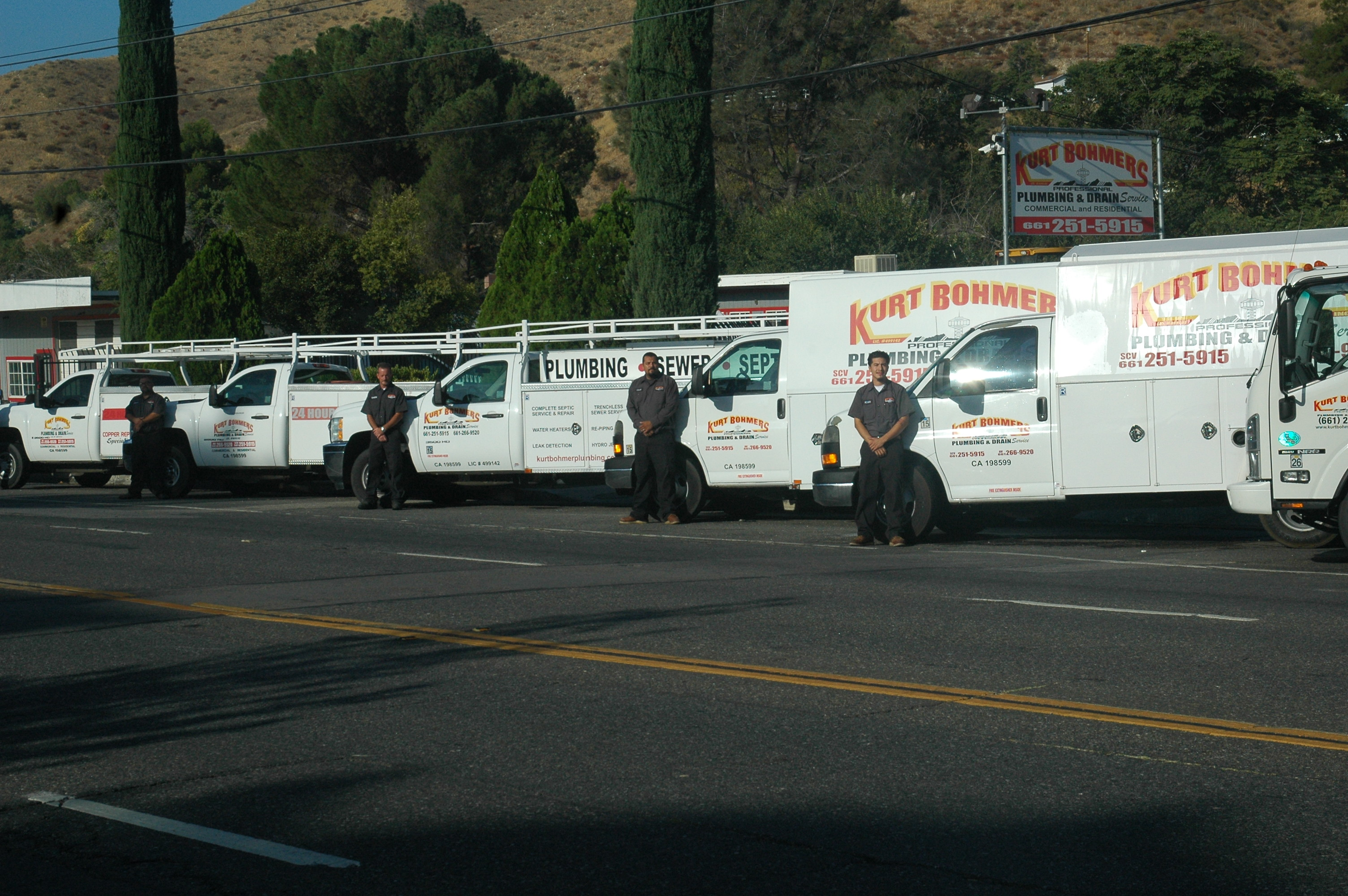 Kurt Bohmers Plumbing employees standing in front of their service trucks